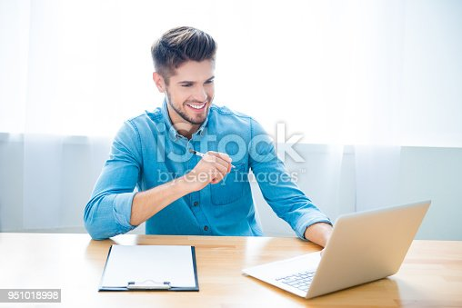 istock Handsome happy young man working on laptop and making notes 951018998