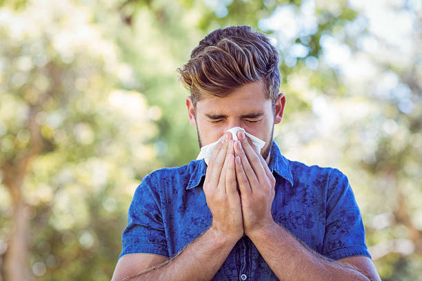 handsome hipster blowing his nose - sneezing bildbanksfoton och bilder