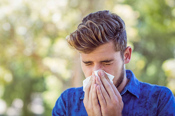 Handsome hipster blowing his nose Handsome hipster blowing his nose on a sunny day human parainfluenza virus stock pictures, royalty-free photos & images