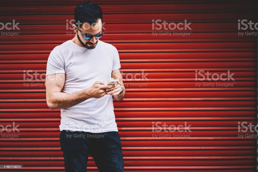 Handsome hipster guy banking via application on mobile phone standing...