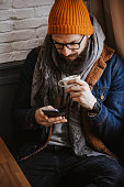 Handsome hipster guy using smart phone in cafe