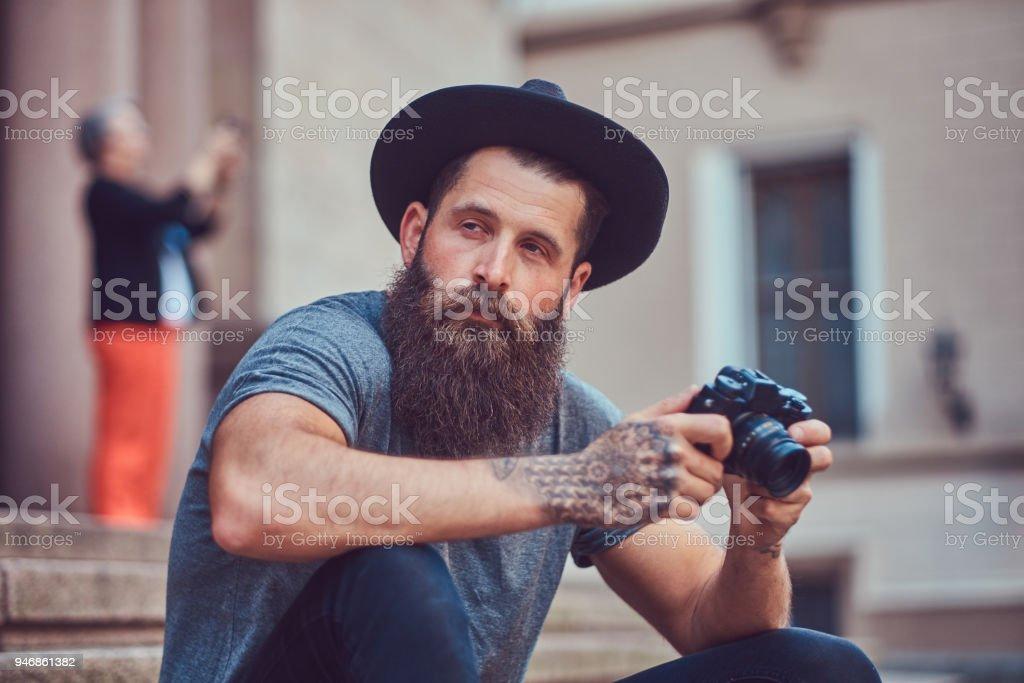 Un hombre guapo hipster con una elegante barba y tatuajes en los brazos  vestido con ropa 7db86a354a6