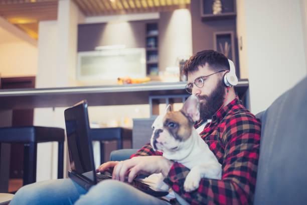 Hübscher Hipster-Mann sitzt mit seinem Hund auf dem Wohnzimmersofa und benutzt einen Laptop – Foto
