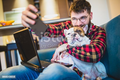 Handsome, hipster man sitting on the livingroom sofa with his dog, taking selfie