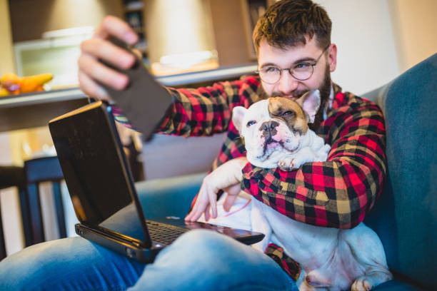 Handsome, hipster man sitting on the livingroom sofa with his dog, taking selfie stock photo