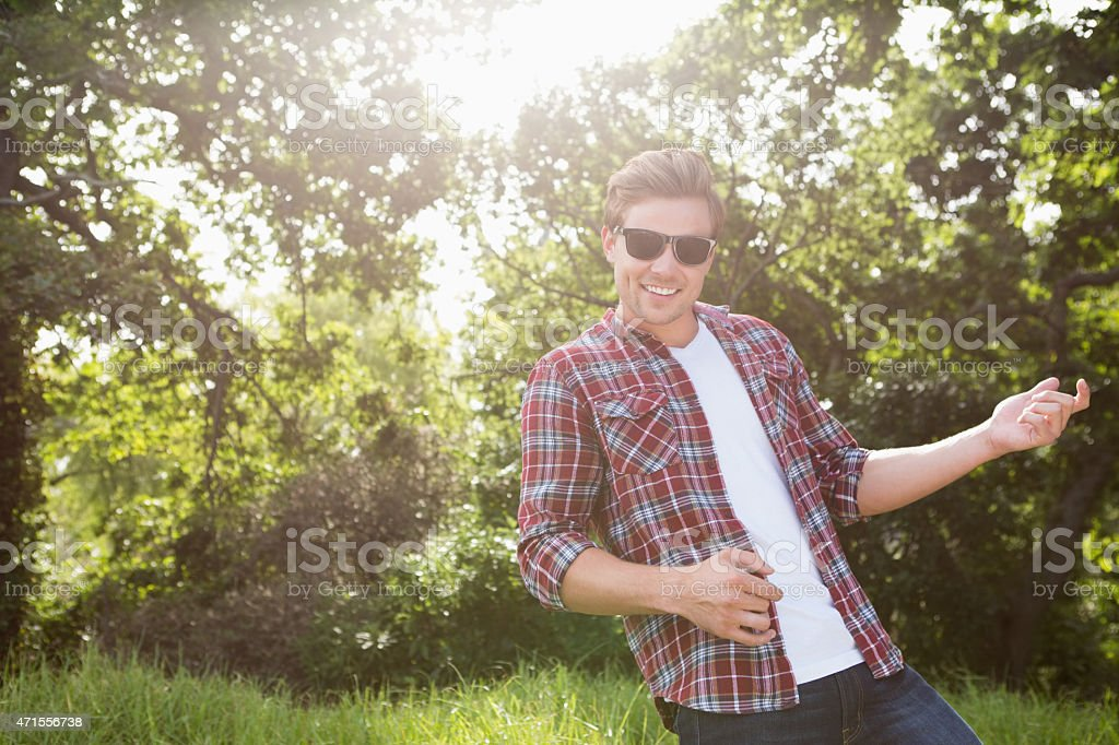 Handsome hipster playing air guitar stock photo