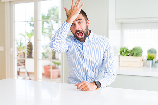 1046559700 istock photo Handsome hispanic business man surprised with hand on head for mistake, remember error. Forgot, bad memory concept. 1205748825