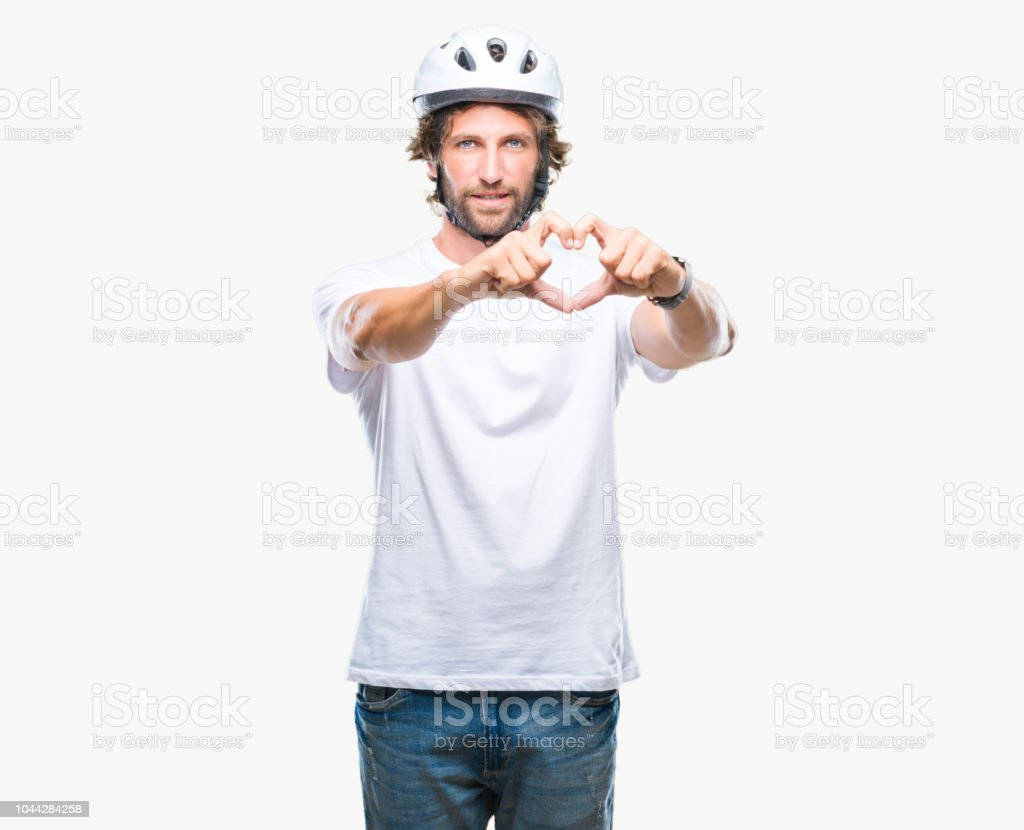Handsome hispanic cyclist man wearing safety helmet over isolated background smiling in love showing heart symbol and shape with hands. Romantic concept. stock photo