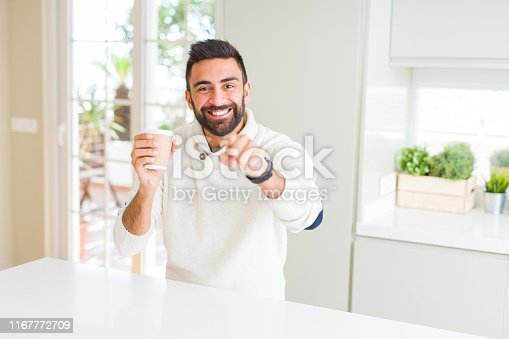 Handsome hispanic man drinking a coffee in a paper cup pointing with finger to the camera and to you, hand sign, positive and confident gesture from the front