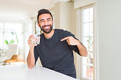 istock Handsome hispanic man drinking a fresh glass of water with surprise face pointing finger to himself 1134255783