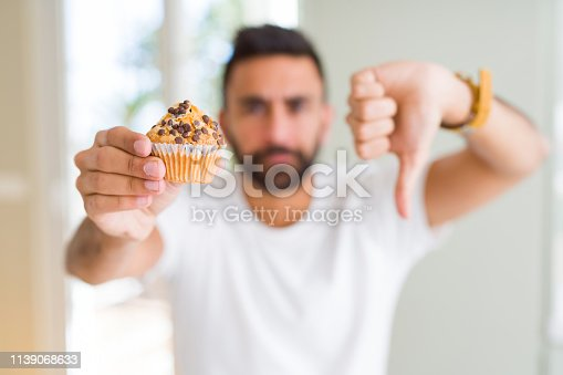 Handsome hispanic man eating chocolate chips muffin with angry face, negative sign showing dislike with thumbs down, rejection concept