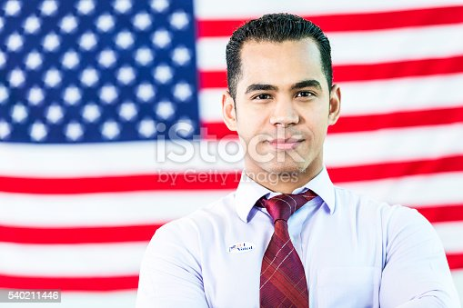 istock Handsome Hispanic Man in front of American flag 540211446