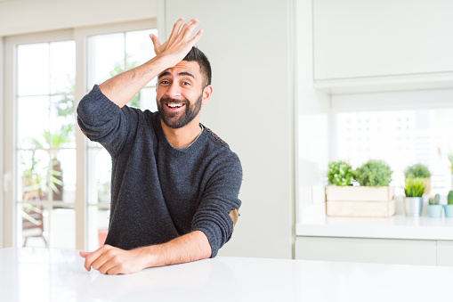 1046559700 istock photo Handsome hispanic man wearing casual sweater at home surprised with hand on head for mistake, remember error. Forgot, bad memory concept. 1134255636