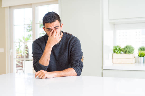 handsome hispanic man wearing casual sweater at home tired rubbing nose and eyes feeling fatigue and headache. stress and frustration concept. - strofinare toccare foto e immagini stock