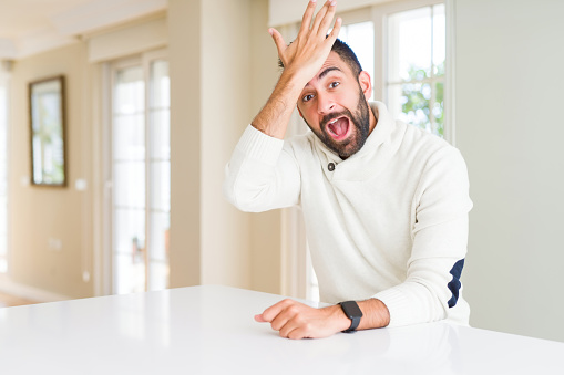 1046559700 istock photo Handsome hispanic man wearing casual white sweater at home surprised with hand on head for mistake, remember error. Forgot, bad memory concept. 1167772862