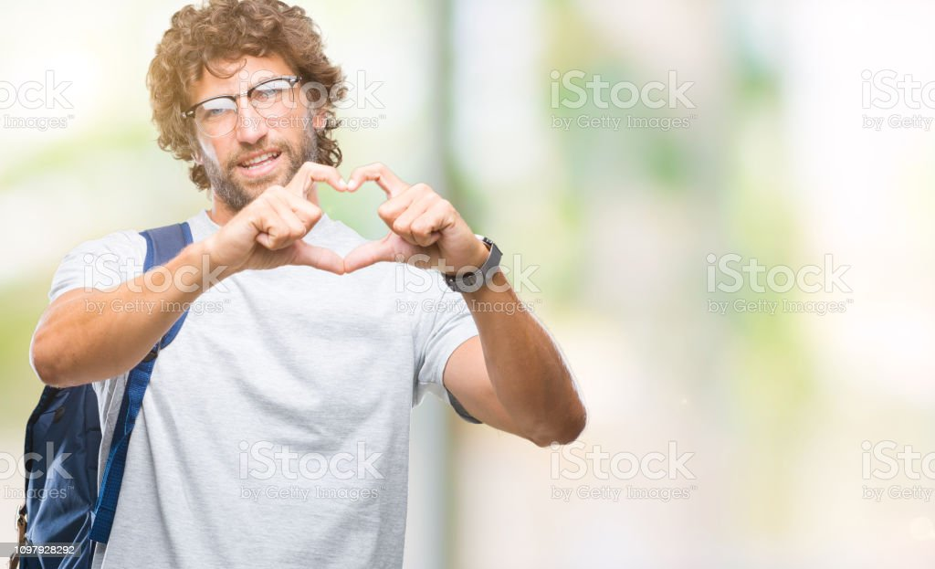 Handsome hispanic student man wearing backpack and glasses over isolated background smiling in love showing heart symbol and shape with hands. Romantic concept. stock photo