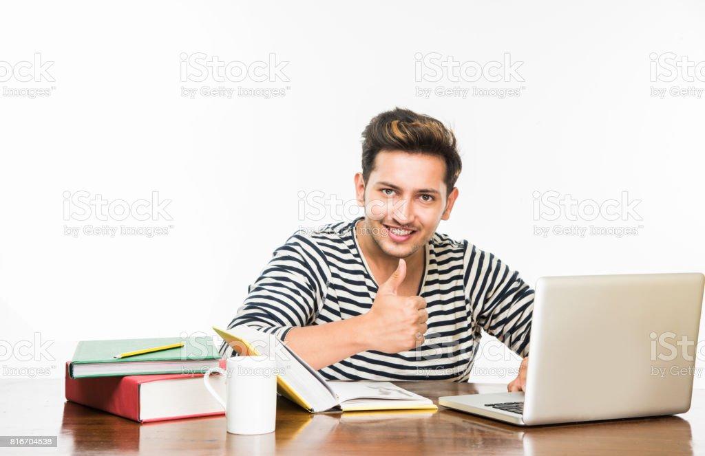 Beau garçon Indien ou mâle Collège étudiant sur table d'étude avec la pile de livres, tasse de café et ordinateur portable. Souriant ou pensant ou inquiet ou montrant des pouces vers le haut ou à l'aide de smartphone - Photo
