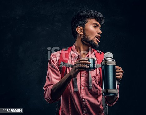 Handsome Indian hiker with backpack got a stirring sensation drinking a tea from a thermos. Studio photo against a dark textured wall