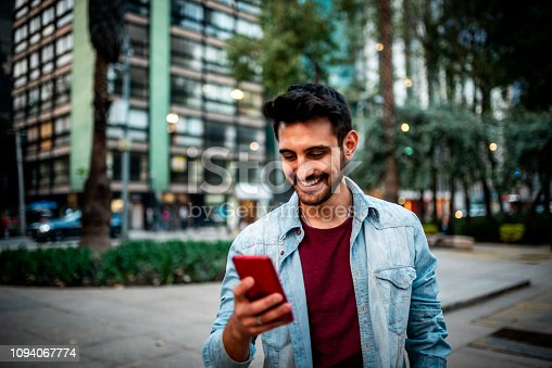 Portrait of a handsome smiling man using mobile phone at the street.
