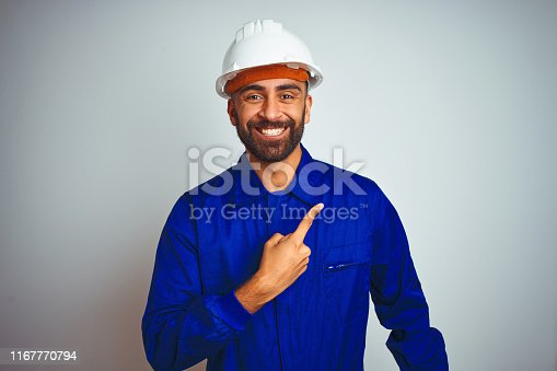istock Handsome indian worker man wearing uniform and helmet over isolated white background cheerful with a smile of face pointing with hand and finger up to the side with happy and natural expression on face 1167770794