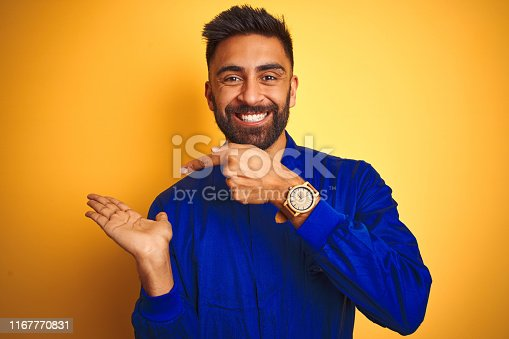1047558948istockphoto Handsome indian worker man wearing uniform over isolated yellow background amazed and smiling to the camera while presenting with hand and pointing with finger. 1167770831
