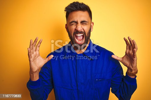 1047558948istockphoto Handsome indian worker man wearing uniform over isolated yellow background celebrating mad and crazy for success with arms raised and closed eyes screaming excited. Winner concept 1167770833