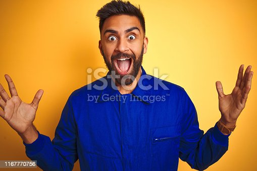 1047558948istockphoto Handsome indian worker man wearing uniform over isolated yellow background celebrating crazy and amazed for success with arms raised and open eyes screaming excited. Winner concept 1167770756
