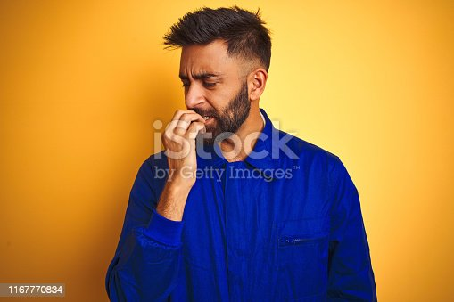 1047558948istockphoto Handsome indian worker man wearing uniform over isolated yellow background looking stressed and nervous with hands on mouth biting nails. Anxiety problem. 1167770834