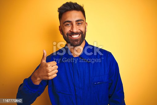 1047558948istockphoto Handsome indian worker man wearing uniform over isolated yellow background doing happy thumbs up gesture with hand. Approving expression looking at the camera with showing success. 1167770842