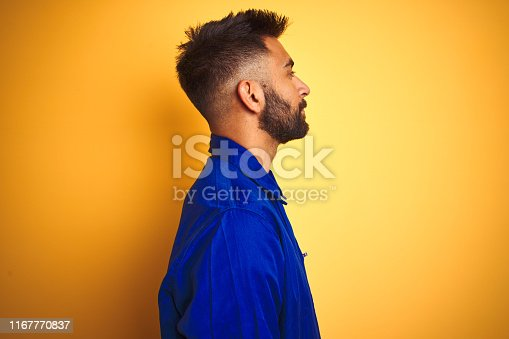 1047558948istockphoto Handsome indian worker man wearing uniform over isolated yellow background looking to side, relax profile pose with natural face with confident smile. 1167770837
