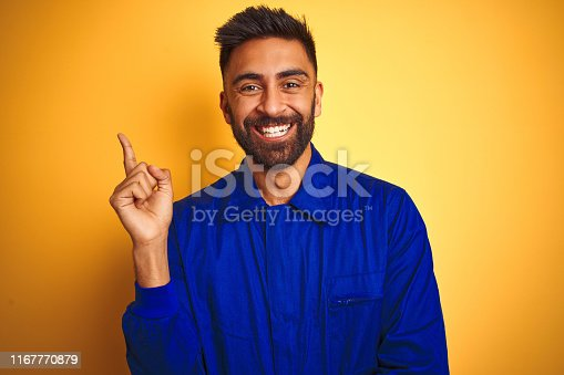 1047558948istockphoto Handsome indian worker man wearing uniform over isolated yellow background with a big smile on face, pointing with hand and finger to the side looking at the camera. 1167770879