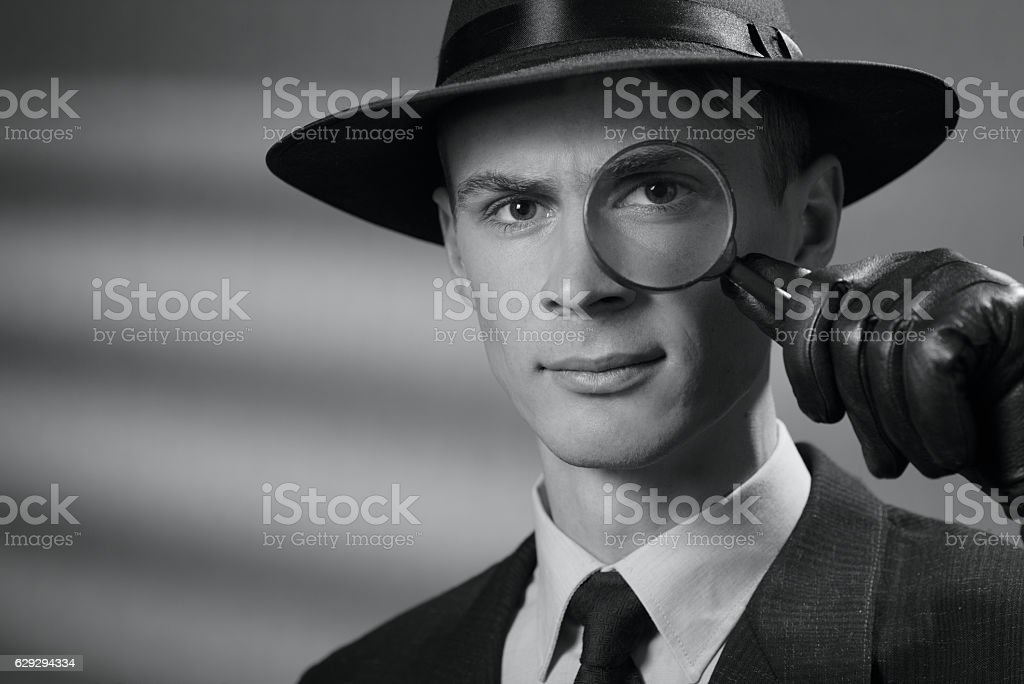 Handsome intelligent young detective in a hat stock photo