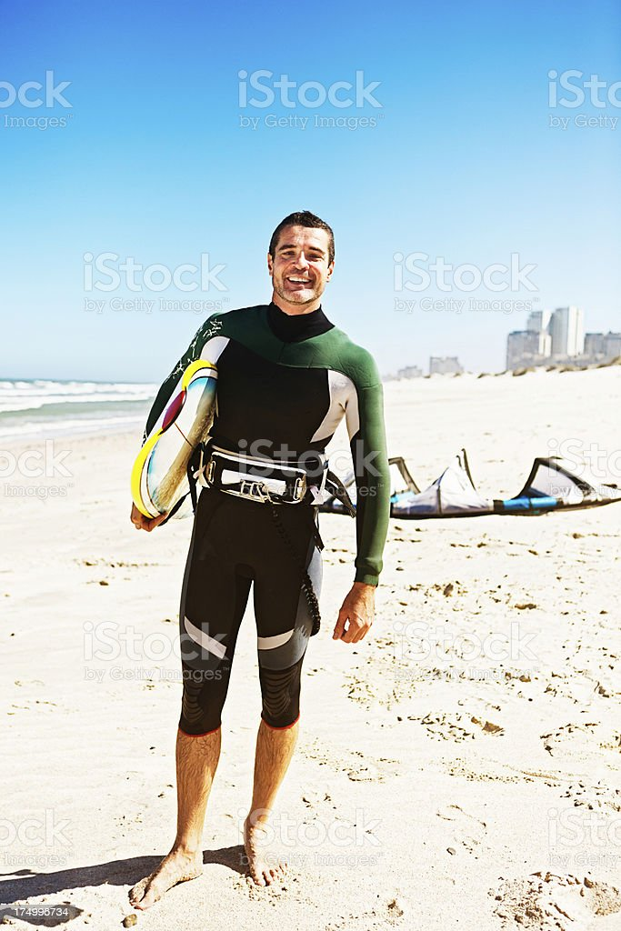 Handsome kiteboarder holding board ready for the surf royalty-free stock photo