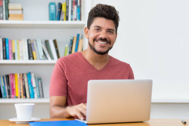 Handsome latin american man with beard working at computer Handsome latin american man with beard working at computer at home spanish and portuguese ethnicity stock pictures, royalty-free photos & images