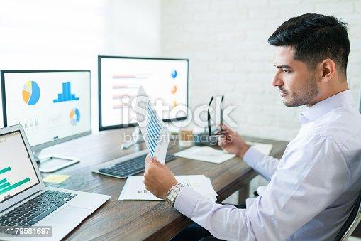 istock Handsome Latin Businessman Examining Sales Data 1179581697