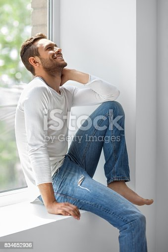 834639402istockphoto Handsome laughing man relaxing on window sill 834652936