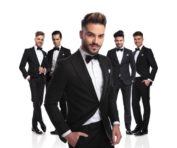 handsome leader of young men in black tuxedoes looking relaxed handsome leader of young men in black tuxedoes standing on white background, looking relaxed tuxedo stock pictures, royalty-free photos & images