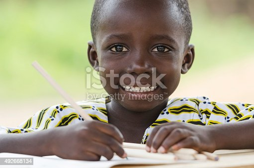 istock Handsome Little African Black Boy Toothy Smile in School Writing 492668134