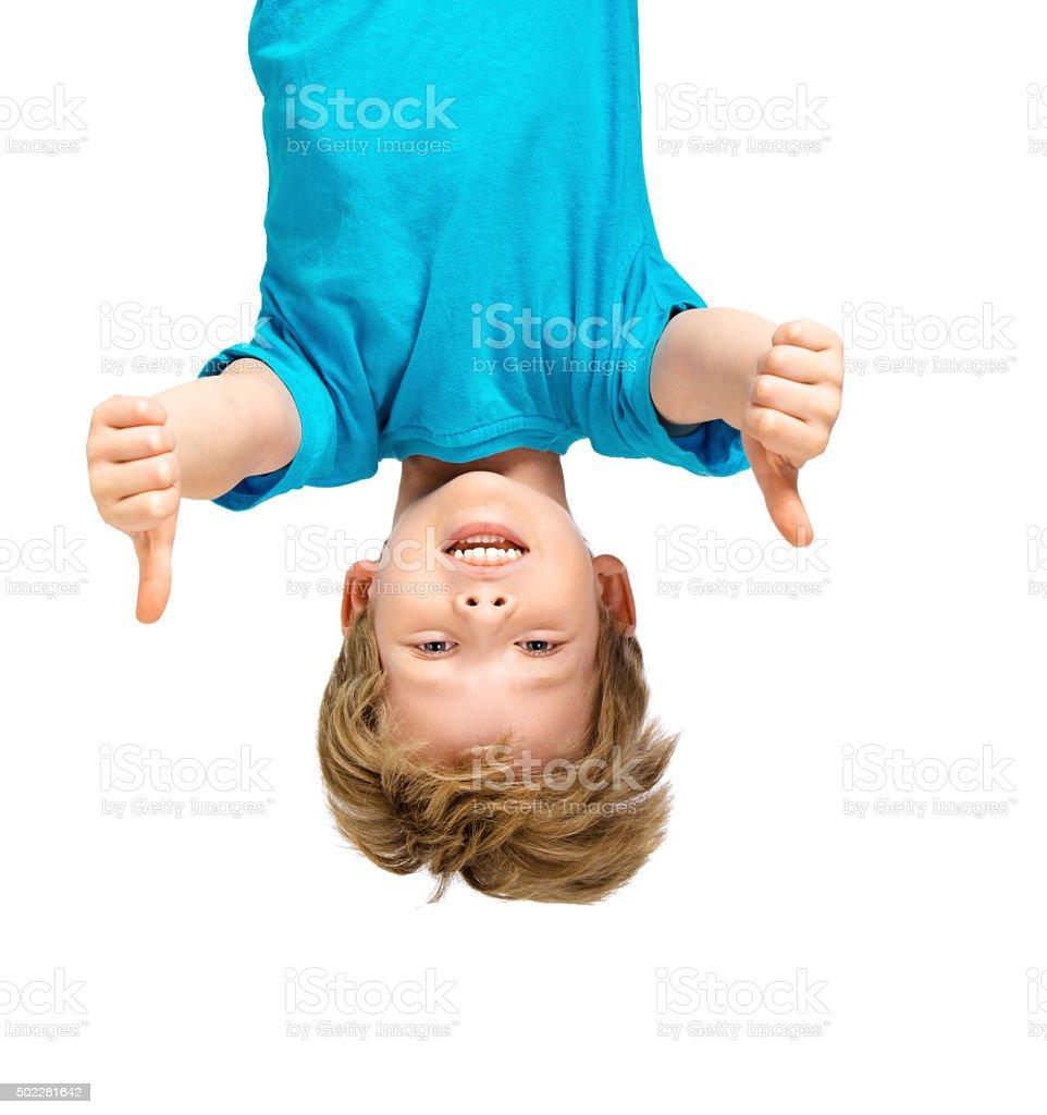 Handsome little boy hanging upside down stock photo