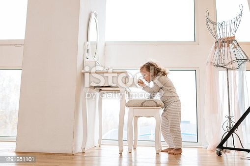 Handsome little girl in pajamas stands near console table with mirror and pulls drawer out of it