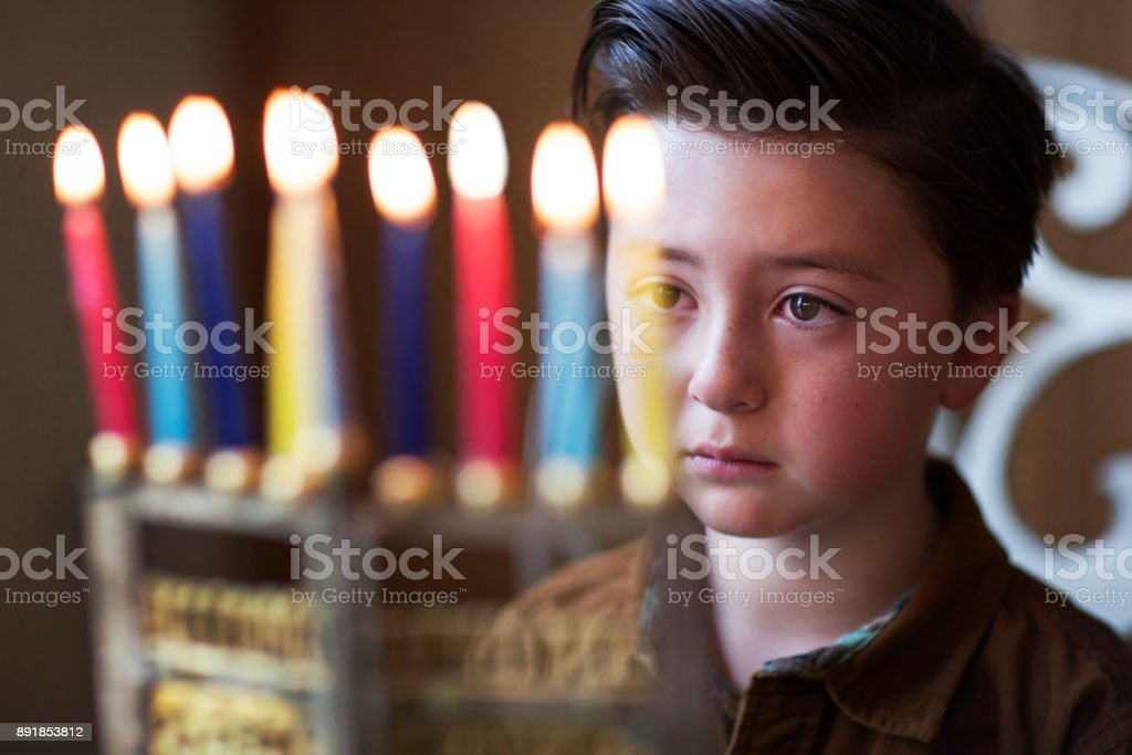 Handsome little Jewish boy with brown styled pompadour staring and meditating on Hanukkah candles in a gold menorah during Hanukkah light festival stock photo