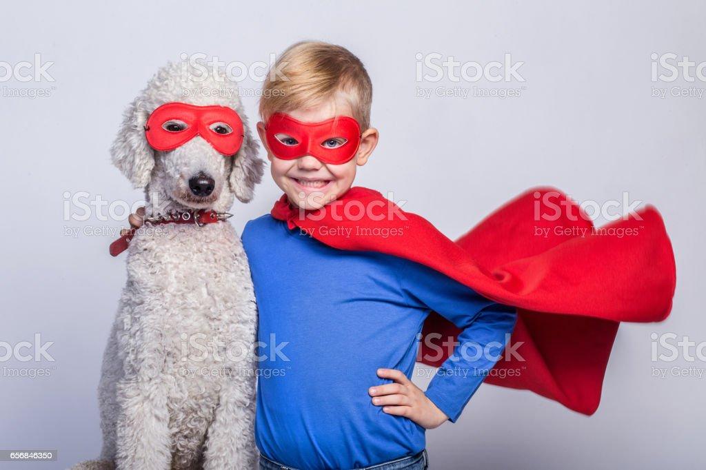 Handsome little superman with dog. Superhero. Halloween. Studio portrait over white background stock photo