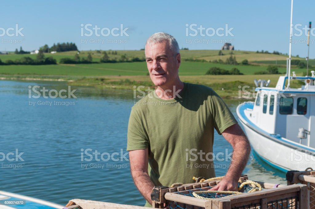 Handsome Lobsterman with Traps on Boat stock photo