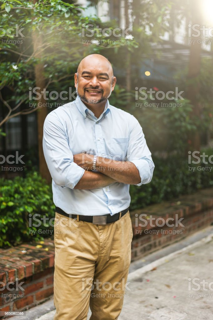 Handsome Malay businessman looking at camera in front of workspace royalty-free stock photo