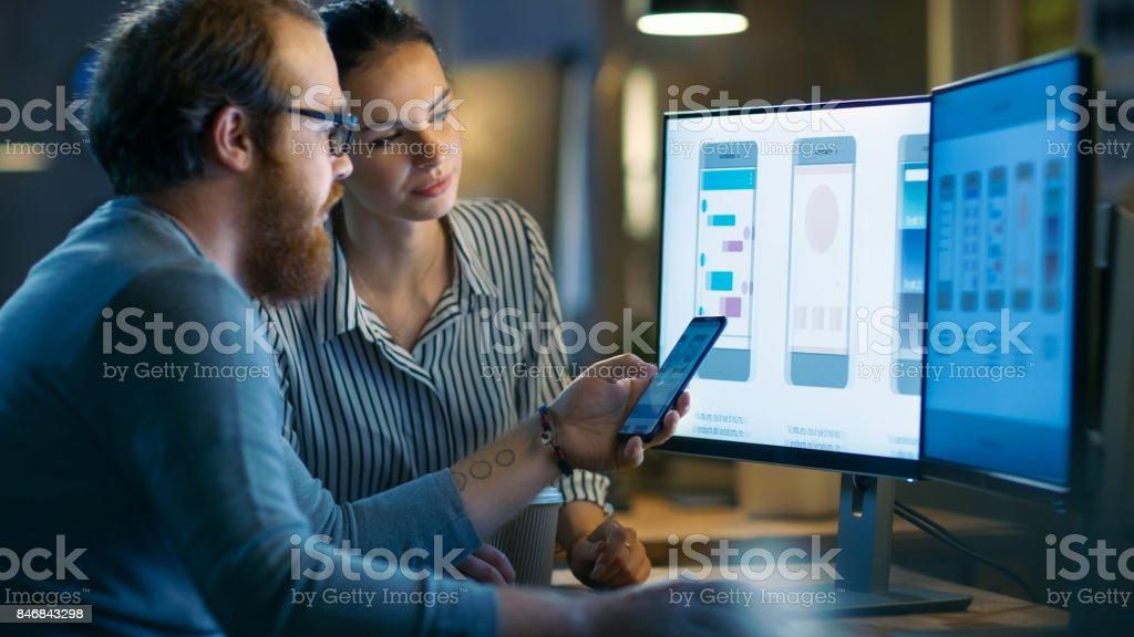 Yakışıklı erkek ve güzel kadın mobil uygulama tasarımcılarının Test etmek ve yeni App özellikleri tartışmak. Bir kişisel bilgisayar ile diğer yetenekli insanlarla paylaştıkları yaratıcı bir Office uzayda iki göstermek üzerinde çalışırlar. stok fotoğrafı