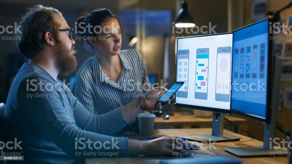 Handsome Male and Beautiful Female Mobile Application Designers Test and Discuss New App Features. They Work on a Personal Computer with Two Displays, in a Creative Office Space they Share with Other Talented People. stock photo