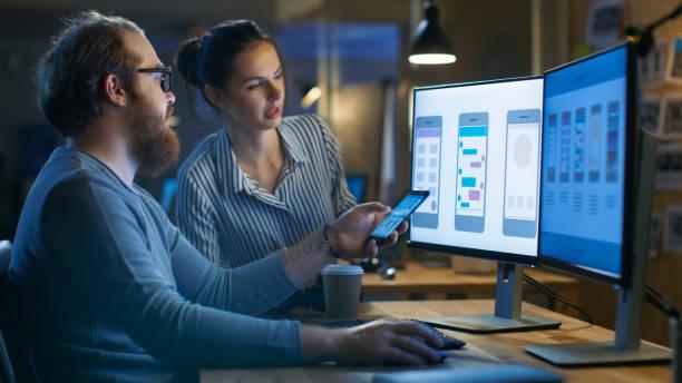 ハンサムな男性と美しい女性のモバイル アプリケーション デザイナーはテストし、新しいアプリの機能について説明します。彼らは彼ら他の才能のある人々 と共有する創造的なオフィス空間における 2 つのディスプレイとパソコンで動作します。 ストックフォト