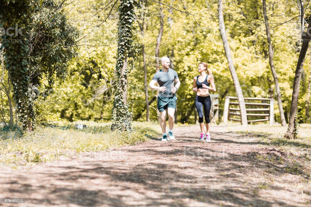 Handsome male and cute girl, jogging in the park royalty-free stock photo