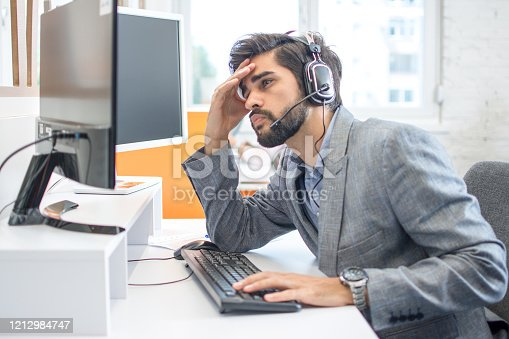 932342408istockphoto Handsome male Call center operator with headset suffering from headache 1212984747