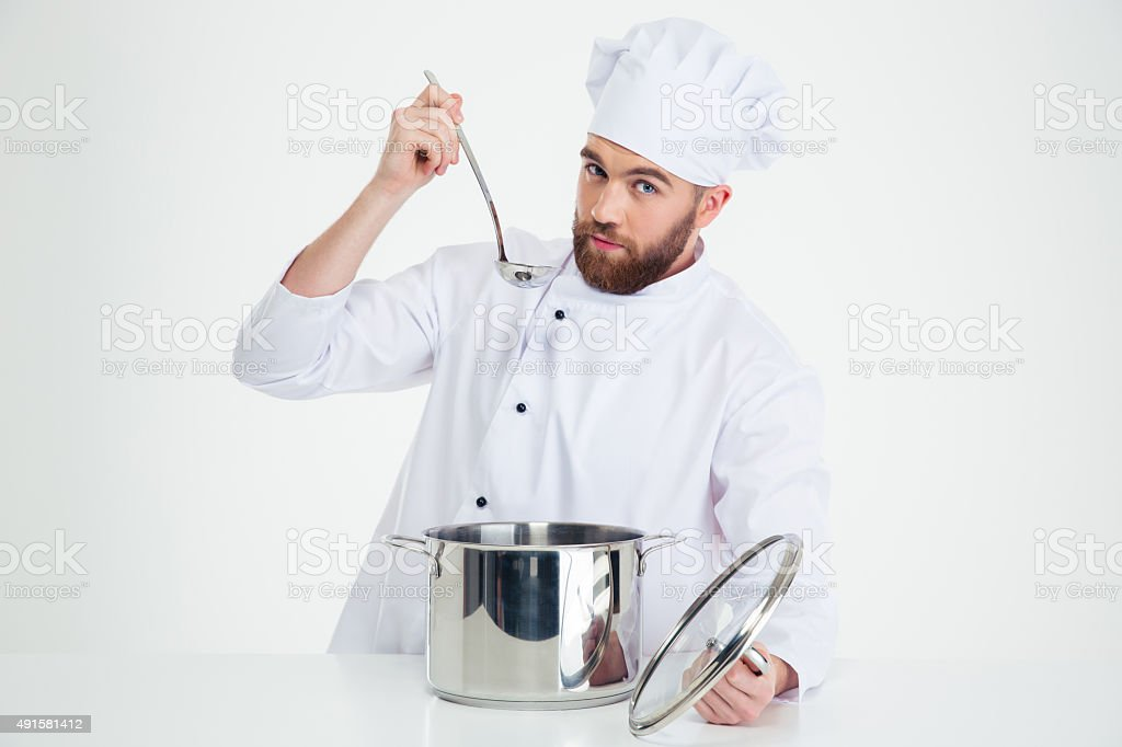 Handsome male chef cook tasting food stock photo